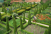A musician walks through the ornamental garden at Garsington Manor, Oxfordshire, before a rehearsal of Garsington Opera.