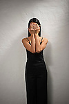 Asian woman covering her eyes with her hands