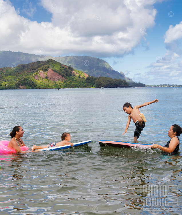 A family plays in Hanalei Bay off of Hanalei Beach, Kaua'i (Note: Children are model released, adults are not model released).