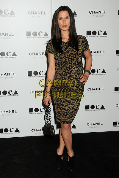"RHONA MITRA .attending MOCA's Annual Gala, ""The Artist's Museum Happening"", Sponsored by Chanel Fine Jewelry, held at MOCA Grand Avenue (Museum Of Contemporary Art) in Los Angeles, California, USA, November 13th 2010. .full length gold khaki black print dress green hand on hip bag handbag chain handle strap shoes ankle boots shooboots .CAP/ADM/BP.©Byron Purvis/AdMedia/Capital Pictures."