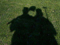 Shadows of couple hold shovel and hoe cast on grass in theiir home.