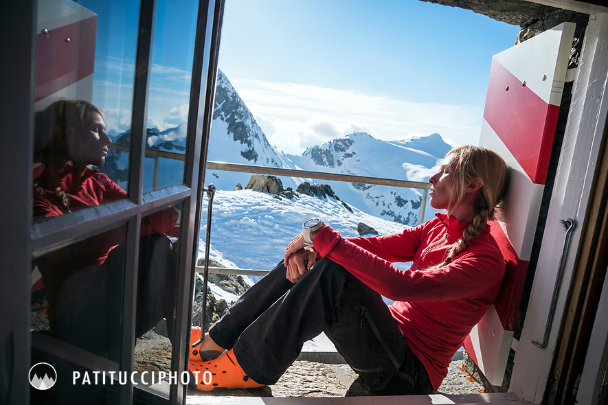 A woman sits in the window of the Tierbergli Hut relaxing in the sun while on a ski tour of the Berner Haute Route, Switzerland