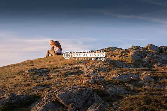 A woman sits alone on Porth Island in Newquay, Cornwall.