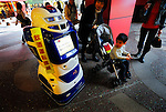 Children look at ALSOK's Reborg-Q  security robot, which provides local information via its touch-screen panel, at Canal City shopping and entertainment mall in Fukuoka City, Japan.