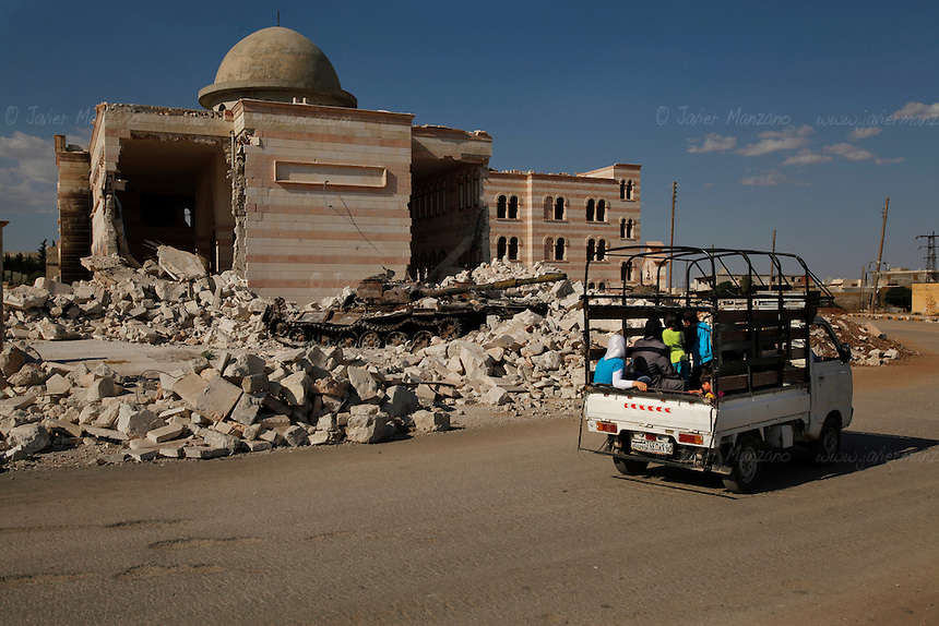 Residents of the northern Syrian town of Az'az drive by the remains of a mosque destroyed during heavy fighting between regime forces and opposition groups in early August of 2012...© Javier Manzano