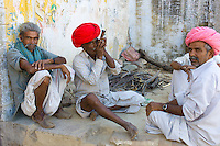 Indian man in traditional clothing smokes clay pipe while sitting with friends in Narlai village in Rajasthan, Northern India