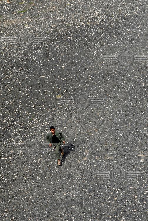 A pupil runs across a school playground..