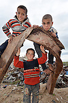 Bilal Al-Shawish (left), 7, and his brothers Mohanad (right), 9, and Mohamed (below), 5, climb on the twisted rubble of what was once a greenhouse before the Israeli bombing of their family's farm in Johor Al-Deek, a section of the Bureij refugee camp in Gaza. The farm is being reactivated today with help from a new well and water pump provided by Dan Church Aid--a member of the ACT Alliance--to replace a well and pump destroyed by the Israeli military during Operation cast Lead.