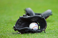 An ACC baseball sits in a glove prior to the game between the Wake Forest Demon Deacons and the North Carolina State Wolfpack at Doak Field at Dail Park on March 17, 2012 in Raleigh, North Carolina.  The Wolfpack defeated the Demon Deacons 6-2.  (Brian Westerholt/Four Seam Images)
