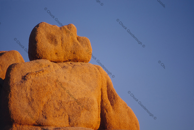 Stock Photo of sandstone boulders on a cliff face in warm, late afternoon sunlight.