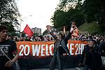 "GERMANY, Hamburg, protest rally ""G-20 WELCOME TO HELL"" against G-20 summit in july 2017, black block with mummed people, woman in leather clothes with beer bottle /DEUTSCHLAND, Hamburg, Landungsbruecken, Protest Demo WELCOME TO HELL gegen G20 Gipfel , vermummte Demonstranten des schwarzen Block,  rechts mit Ledermuetze Andreas Beuth, Anwalt des linksalternativen Zentrums ""Rote Flora"""