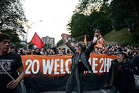 "GERMANY, Hamburg, protest rally ""G-20 WELCOME TO HELL"" against G-20 summit in july 2017, black block with mummed people, woman in leather clothes with beer bottle /DEUTSCHLAND, Hamburg, Landungsbruecken, Protest Demo WELCOME TO HELL gegen G20 Gipfel , vermummte Demonstranten des schwarzen Block,  rechts mit Ledermuetze Andreas Beuth, Anwalt des linksalternativen Zentrums ""Rote Flora"""