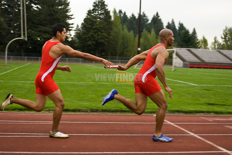Two Men Running a Relay Race on a Track
