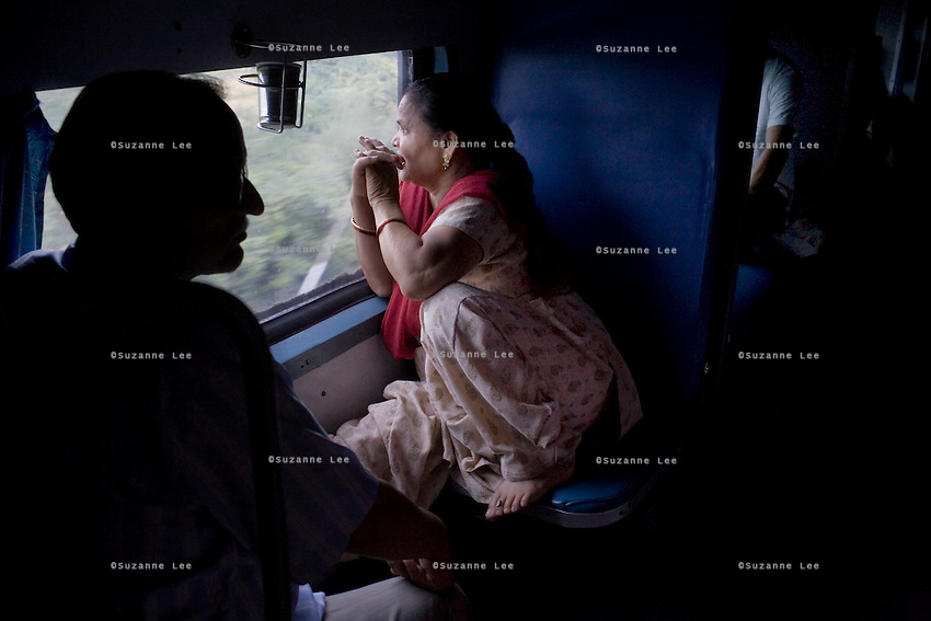 Train passengers look out the glass windows of the a/c coach on the Himsagar Express 6318 as it rains in Tamil Nadu on 9th July 2009.. .6318 / Himsagar Express, India's longest single train journey, spanning 3720 kms, going from the mountains (Hima) to the seas (Sagar), from Jammu and Kashmir state of the Indian Himalayas to Kanyakumari, which is the southern most tip of India...Photo by Suzanne Lee / for The National