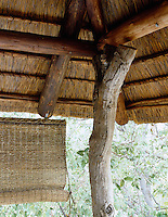 A wooden pillar fashioned out of a tree trunk supports the thatched roof over one of the terraces