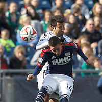 Vancouver Whitecaps FC defender Steven Beitashour (33) and New England Revolution midfielder Diego Fagundez (14) battle for head ball.  In a Major League Soccer (MLS) match, the New England Revolution (blue/white) tied Vancouver Whitecaps FC (white), 0-0, at Gillette Stadium on March 22, 2014.