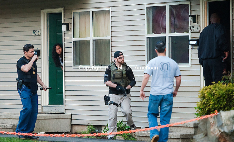 WATERBURY, CT 09 MAY 2013--050913JS01-A neighbor looks out her door as Waterbury police along with probation officers and U.S. Marshals, attempt to serve a warrant at 175 Stonefield Drive in Waterbury on Thursday. Officers searched for men and women wanted for manslaughter, burglary, serious assaults and low to mid-level drug crimes Thursday throughout the city. Police operation was expected to continue into late Thursday and possibly into Friday. .Jim Shannon Republican-American