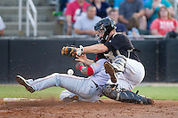 Kannapolis Intimidators catcher Jeremy Dowdy (25) can't hold on to the ball as Wilmer Difo (6) of the Hagerstown Suns slides into home plate at CMC-Northeast Stadium on May 31, 2014 in Kannapolis, North Carolina.  The Intimidators defeated the Suns 4-3 in game two of a double-header.  (Brian Westerholt/Four Seam Images)