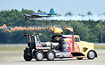 (Chicopee, MA, 07/15/18) Shockwave Jet Truck races down the runway as aerobatics pilot Bill Stein flies past during the Great New England Air and Space Show at Westover Air Reserve Base in Chicopee on Sunday, July 15, 2018. Photo by Christopher Evans