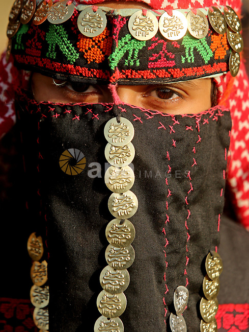 A Palestinian bedouin girl wears traditional dress and poses for a photo during a rally marking the 41st anniversary of Land Day, in Deir el-Balah, Central Gaza Strip, on March 31, 2017.  Land Day marks the killing of six Arab Israelis during 1976 demonstrations against Israeli confiscations of Arab land. Photo by Ashraf Amra