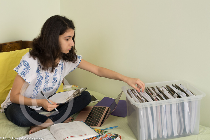 18 year old teenage girl at home, in bedroom at home, doing homework, reaching to get something out of folder in filebox