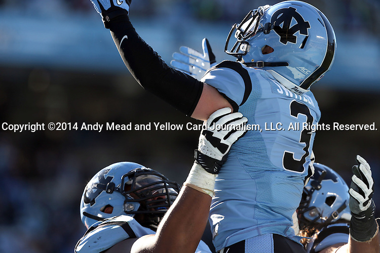 15 November 2014: UNC's Ryan Switzer (3) is hoisted in the air while celebrating his touchdown with teammates Landon Turner (left) and John Ferranto (right). The University of North Carolina Tar Heels hosted the University of Pittsburgh Panthers at Kenan Memorial Stadium in Chapel Hill, North Carolina in a 2014 NCAA Division I College Football game. UNC won the game 40-35.