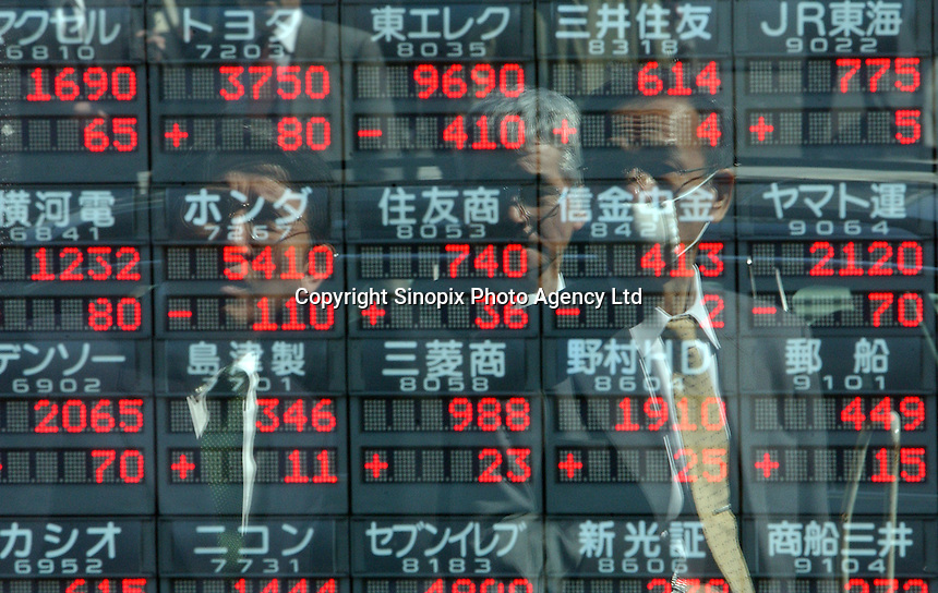 Businessmen are reflected in a stock market sign board in the window a securities company in the business and banking district of Tokyo..