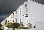 Terraced housing in Falmouth, Cornwall, England, UK with storm clouds overhead