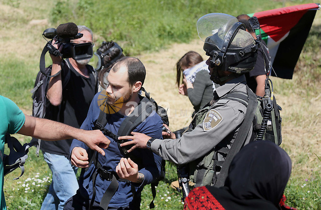 A Palestinian protester scuffles with Israeli border guards during clashes following a march against Palestinian land confiscation on April 1, 2016 in the West Bank village of Nabi Saleh near Ramallah. Photo by Hamza Shalash