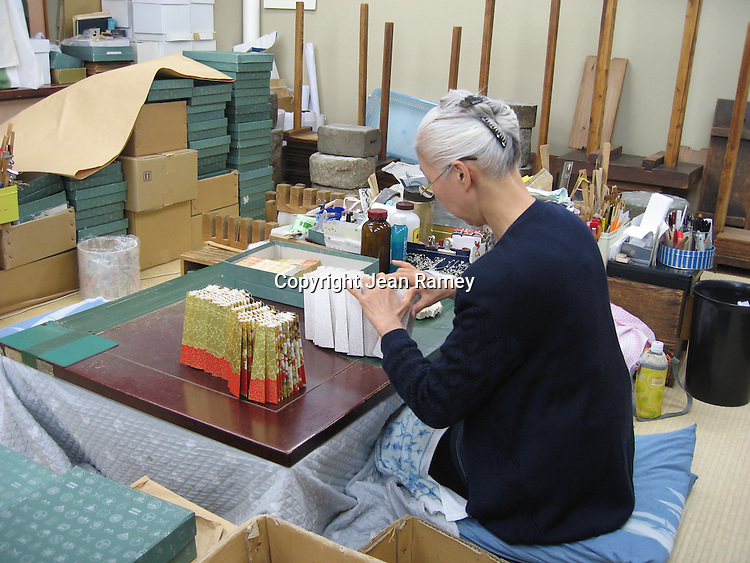 A craftswoman makes delicate paper fans by hand in the old tradition, Kyoto