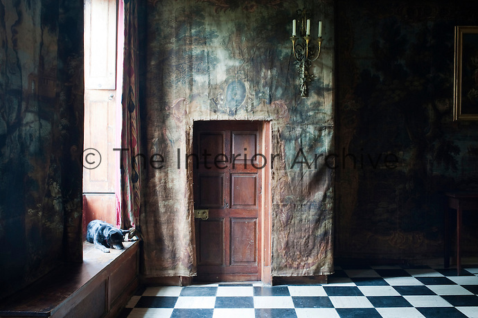 Faded 17th century canvas tapestries partially conceal a door in one of the reception rooms