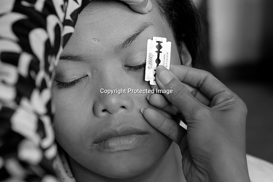 Children of Bassac. Teacher Nop Thyda is shaving the eyebrows of Chanty. The skin of a dancer must be perfect before performing. Phnom Penh, Cambodia - 2007