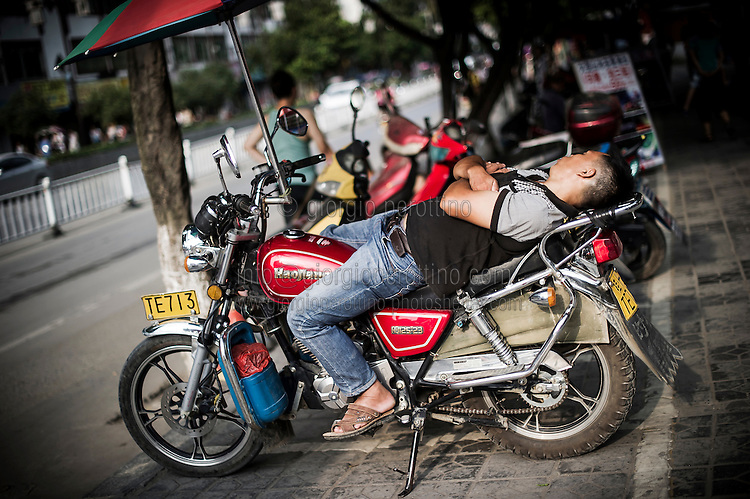 """A Chinese motorbike taxi driver takes a rest on his motorbike's seat in YangShuo near Guilin, China, August 01, 2014. <br /> <br /> This image is part of the series """"24/7"""", an ironic view on restless and fast-growing Chinese economy described through street vendors and workers sleeping during their commercial daily activity. <br /> <br /> © Giorgio Perottino"""