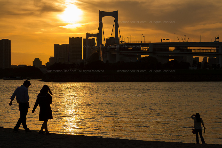 People enjoy the view of Rainbow Bridge from a beach in Odaiba, Tokyo, Japan. Thursday, may 30th 2019
