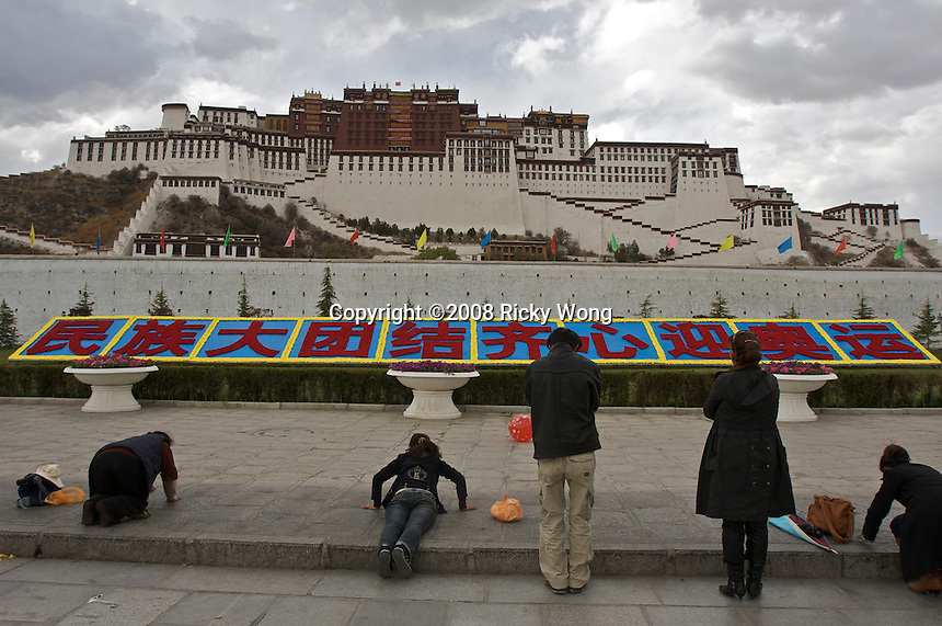 "Worshipers pray by lying on ground facing The Potala Palace in The Potola Palace Square where a big slogan reads ""Big ethnic reunion, allied to welcome the Olympic Games"" in Lhasa, Tibet Autonomous Region, China. The March 14 incident at Lhasa that left the Tibet burning and claimed about 18 lives and injured hundreds, now seems to have affected businesses by more than 50 percent after Tibet reopened to foreign tourists..01 May 2008"