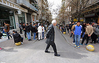 Pictured: An Athenian man walks past dozens of gathered migrants in Heyden Street, Victoria Square Tuesday 08 March 2016<br /> Re: Migrants at Victoria Square, in central Athens, Greece.