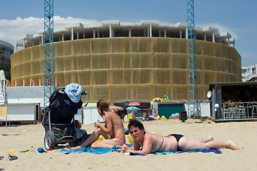 Sunny Beach, Nesebar, Bulgaria..Holidaymakers in front of an unfinished apartment and hotel complex at Sunny Beach, the largest holiday resort in the Balkans, and a popular destination for cheap foreign package tours. Rapid overdevelopment of the Back Sea coast has led to widespread environmental destruction, and many properties lie uncompleted or empty.