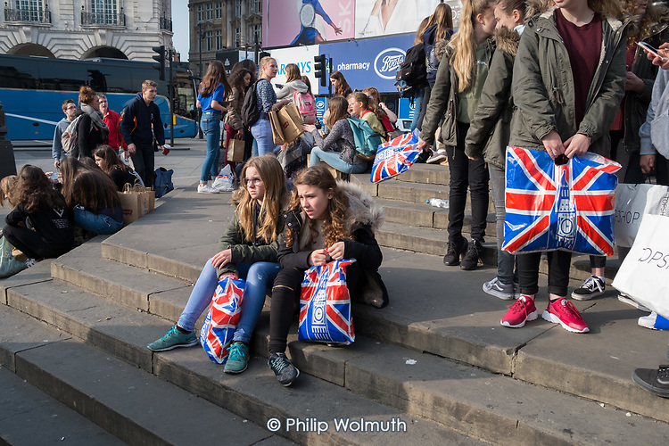 French school pupils on a school trip at Piccadilly Circus, London.