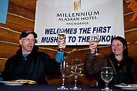 Jeff King toasts his Millenium Hotel *First to the Yukon River* award with his friend and handler Jamie Kohn during his 7-course dinner inside the Community Center at the village of Ruby during the 2010 Iditarod