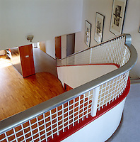 The curved lines of the staircase soften the uncompromising modernist design of the architecture