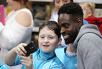 Pictured: Nathan Dyer has a selfie taken by a young boy at the till Wednesday 08 December 2016<br />Re: Swansea City FC players have bought Christmas gifts for 60 children at Smyths toy store in Swansea, south Wales.