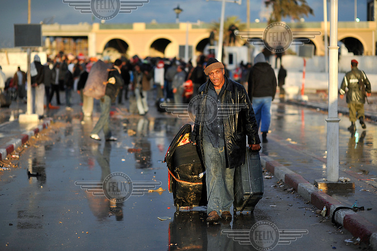 An Egyptian refugee, fleeing from the unrest in Libya, wheels his luggage into Tunisia from the Ra's Ajdir border post. Thousands of people, mostly Egyptian migrant workers, are still waiting to be admitted into Tunisia, resulting in chaos at the border. In recent days an estimated 70,000 refugees have crossed into Tunisia fleeing the hostilities in Libya and raising the spectre of a humanitarian crisis at the border.