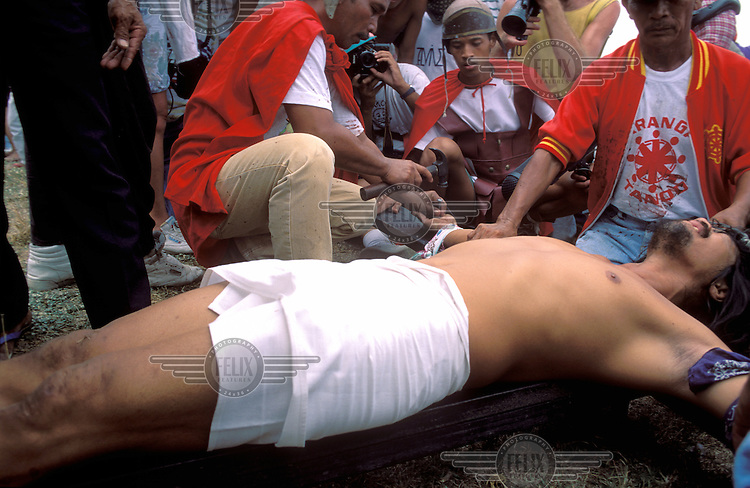 © Martin Flitman / Panos Pictures..San Fernando, PHILIPPINES..Easter celebrations: a man is nailed to the cross.