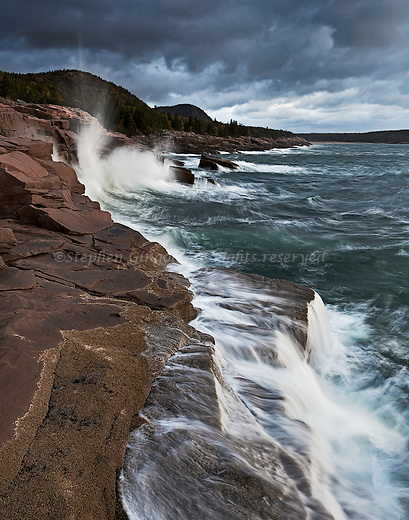 Waves crash against Otter Cliffs on a rainy day at Acadia National Park in Maine.