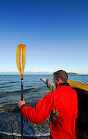Male paddler in yellow kayak and red paddling jacket holding kayak on shoulder, Sea Kayaking the San Juan Islands, WA.