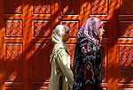 Muslim women passing carved door in old medina of Fes, Morocco