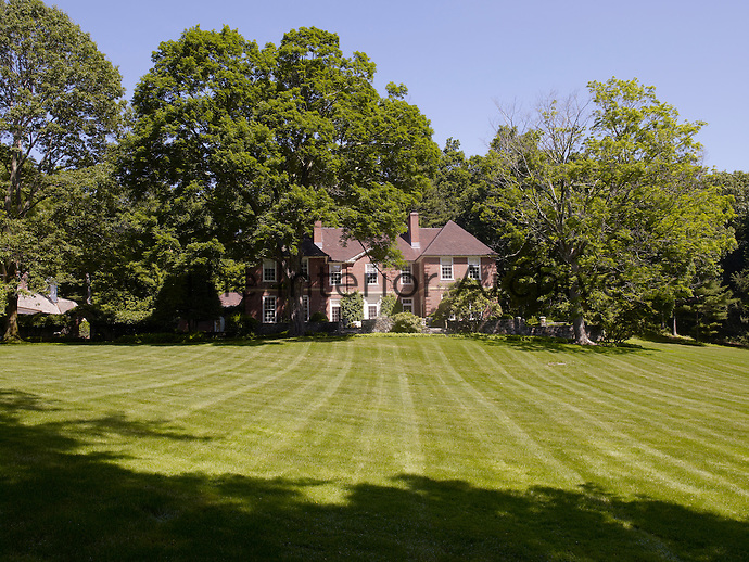 View of the elegant red brick house which was built in the 1930s from across the park