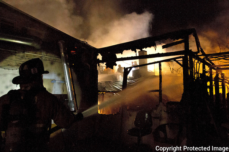 San Diego Fire Department firefighter Tuan Dinh, left, helps battle a two-alarm fire at industrial buildings in San Diego in November, 2012.  photo for U-T San Diego