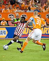 Chivas USA fmidfielder Michael Lahoud (27) attempts to dribble around Houston Dynamo defender Andrew Hainault (31).  Houston Dynamo defeated CD Chivas USA 1-0 at Robertson Stadium in Houston, TX on June 10, 2009.