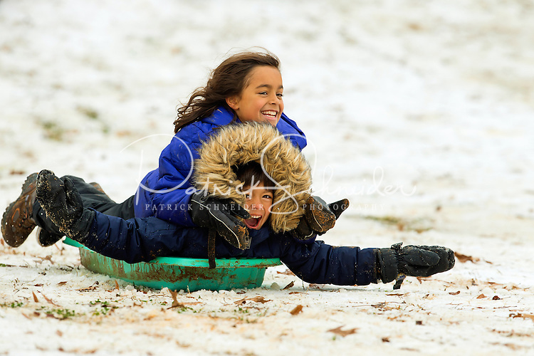 Charlotte Snow Photography - Photography of two kids having fun riding their snow sled on hill in Charlotte, North Carolina neighborhood. <br /> Snow fun in Charlotte North Carolina.<br /> <br /> Charlotte Photographer - PatrickSchneiderPhoto.com